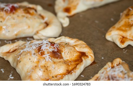Calzone pizza as baked polish pierogi. Fresh precooked stuffing wrapped in semolina flour dough covered with tomato cause, sprinkled with parmesan and painted with red olive oil.