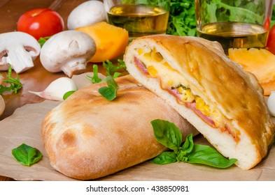 Calzone pizza with ham , mushrooms and corn