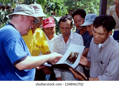 Cam Lo, Quang Tri Province / Vietnam - July 29, 2002: Cam Lo residents viewing photos a returning Vietnam War veteran took while stationed in the area in 1967.