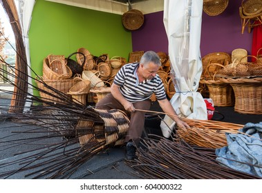 CAMACHA, MADEIRA, PORTUGAL - SEPTEMBER 10, 2016:  A basket weaver at work in the factory shop in Camacha Madeira Portugal
