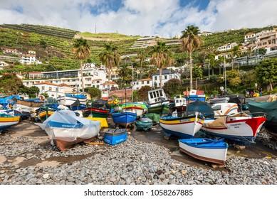 Camara de Lobos, Madeira, Portugal - December 10, 2016: Colorful fishing boats on the shore of fishing village Camara de Lobos near Funchal, Madeira Island, Portugal.