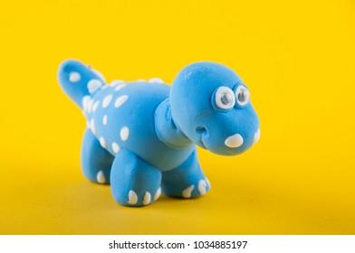 Camarasaurus. Blue play dough dino figure on yellow background