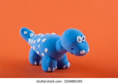 Camarasaurus. Blue, white dino model made of plasticine on orange background