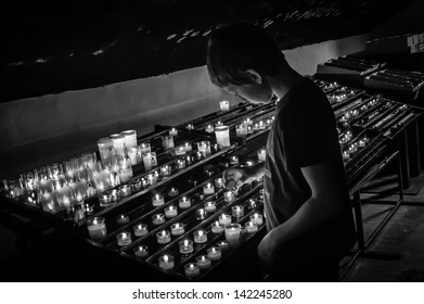 CAMARGUE, FRANCE - MAY 2: Unidentified boy lights candle in church as seen on May 2, 2013 in Camargue, France. France is home to second largest population of Roman Catholics in Europe.