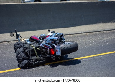 Camarillo, California / USA -  July 2, 2020: A mortorcycle lies on its side after a collision by a downed motorcyclist in the Conejo Pass, Northbound lane.  The motorcyclist was injured in the crash.