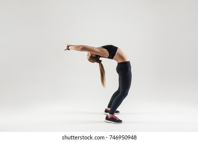 Camatkarasana. Bridge pose. Athletic woman doing yoga. Indoor shot