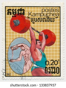 CAMBODIA - CIRCA 1987: A stamp printed in Kampuchea, shows ancient and modern weightlifter, circa 1987