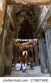 Cambodia; February 2020: Statue of stone buddha with shoulder covered by yellow fabrics. Colorful flags hanging from ceiling, buddhist people pray on the floor. Banteay Kdei temple, Angkor, Siem Reap