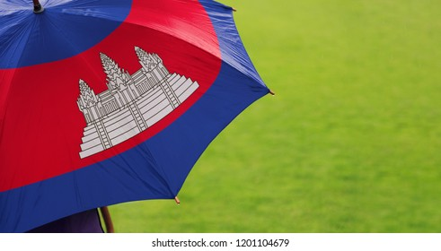 Cambodia flag umbrella. Closeup of printed umbrella over green grass field background. Landscape, side view. Rainy weather/ climate change and global warming concept.