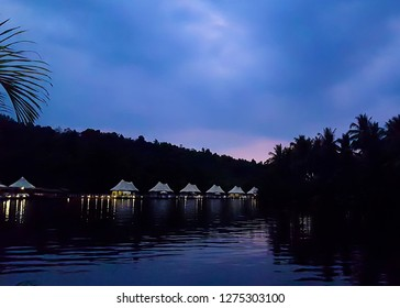 Cambodia, Koh-Kong - March : 4 rivers tented jungle ecotourism hotel coming into view around a bend in the Kong River at twilight
