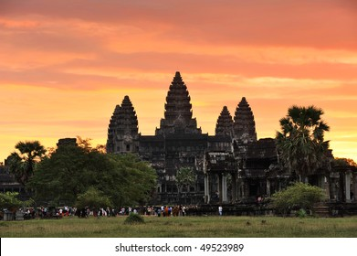 Cambodia. Siem Reap. Awaking Angkor wat temple against the colourful fiery sunrise sky. Crowds of tourists are meeting the sunrise.
