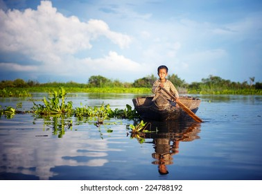 Cambodian boy travelling by boat in his floating village Cambodia.