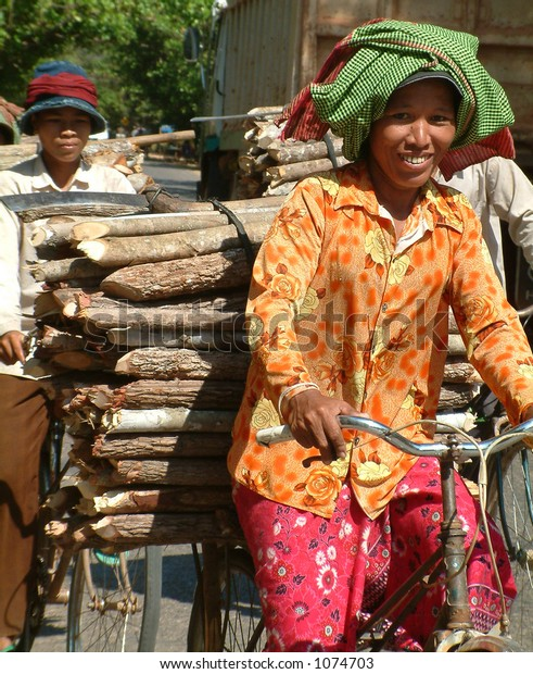 Cambodian lady carrying timber on bicycle