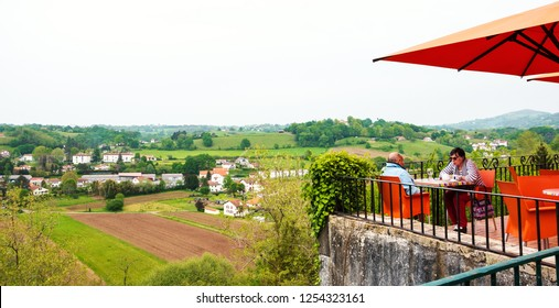 CAMBO-LES-BAINS, FRANCE - AVRIL 19, 2018: Senior couple relaxing in cafe with valley view at Cambo-les-Bains (a charming spa town) promenade. Springtime tourism at French Basque country.