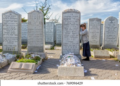Cambria Heights,NY / USA - November 9, 2015: A religious jewish girl prays at graveside of Rebbetzin Chaya Mushka, the Lubavitcher Rebbe's wife at Montefiore Cemetery.