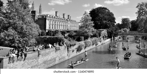 CAMBRIDGE, CAMBRIDGESHIRE, ENGLAND, UK, June 7th 2015, Cambridge University students sit on the wall of Latham Lawn, overlooking the River Cam while people punt along the Backs.