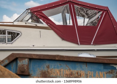 Cambridge, Cambridgeshire, UK - Circa April 2019: Abstract of a large cabin cruiser located at a boat yard, seen behind a large industrial skip. The boat appears to be in the skip itself.