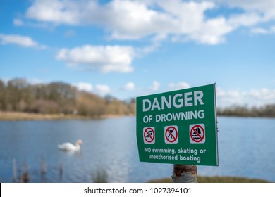 Cambridge, Cambridgeshire, UK - Circa February 2018: Danger of Drowning metal sign seen positioned to a large lake in England. An out of focus, isolated Swan can be seen left of the sign.