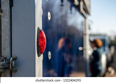 Cambridge, Cambridgeshire, UK - Circa February 2019: Close-up, shallow focus of a rear light seen attached to a horse trailer and box. The foreground shows a horse owner preparing for a journey.