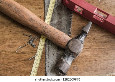 Cambridge, Cambridgeshire, UK - Circa January 2019: Detailed image of common carpentry tools including a metric extended tape measure seen on a wooden work surface located in a workshop area.