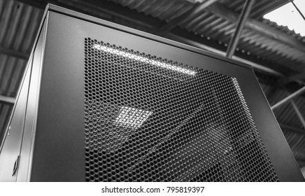 Cambridge, Cambridgeshire, UK - Circa January 2018: Vertical view of a large server cabinet seen within a production facility. Detail of the meshed and vented door is shown as is the internal LED.
