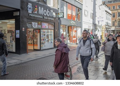 Cambridge, Cambridgeshire, UK - Circa March 2019: Busy High Street on a Saturday, showing shoppers walking the wet streets. A senior woman is seen waiting to cross the road to enter the phone shop.