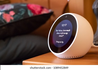 Cambridge, Cambridgeshire, UK - Circa May 2018: Isolated, shallow focus image of a popular Smart Home personal assistant seen on a bedside table. The device is connected to WiFi and streams audio & TV