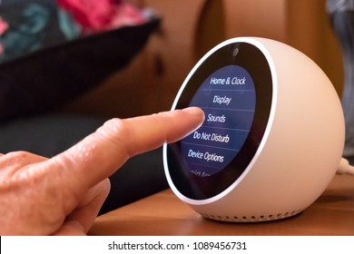 Cambridge, Cambridgeshire, UK - Circa May 2018: Person using there finger to configure a well-known Smart Home assistant on a bedside table. The image shows the configuration and setup screen.