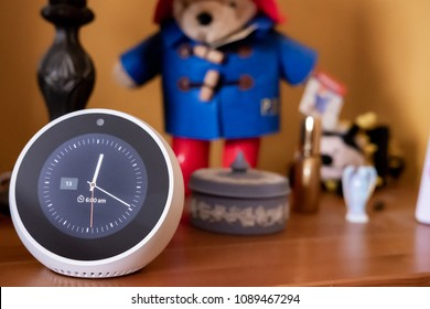 Cambridge, Cambridgeshire, UK - Circa May 2018: Isolated, shallow focus image of a popular Smart Home personal assistant seen on a bedside table. Also seen are a trinket holder and a small toy bear.