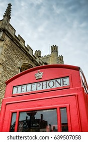 CAMBRIDGE, CAMBRIDGESHIRE, UK - CIRCA MAY 2017: Close-up view of an old styled, British red telephone box with a gold crown above the lettering. Seen in front of a large, city church in the city.