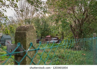 Cambridge, Cambridgeshire, UK - Circa October 2018:  Distant, in focus view of make-shift chicken houses seen in a rural location during the fall. The foreground shows an out of focus wire fence.