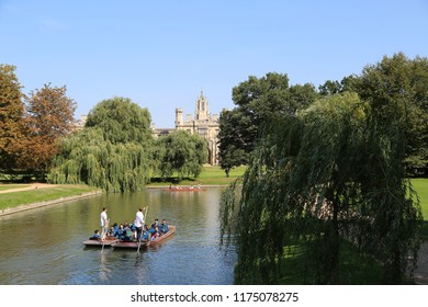 Cambridge, Cambridgeshire / UK - September 1st 2018: Punting on the river cam in Cambridge, college buildings in the background, trees in the foreground