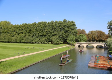 Cambridge, Cambridgeshire / UK - September 1st 2018: Punting on the river cam in Cambridge, old bridge in the background, punts in the foreground