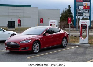 CAMBRIDGE, CANADA - April 16th, 2019: Red Tesla Model S Supercharging at Tesla Supercharger, Cambridge SmartCentres location.