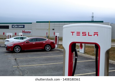 CAMBRIDGE, CANADA - April 16th, 2019: Tesla Supercharger in-front of two charging Tesla Model S's.