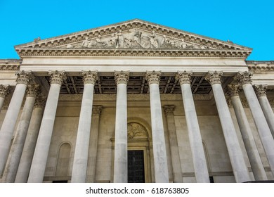 CAMBRIDGE, ENGLAND - MAR 13, 2017: facade of Fitzwilliam Museum in Cambridge from outside with old greek traditional flies at the classic roof gable.