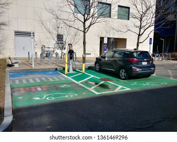 Cambridge, MA - March 16 2019: A Chevrolet Volt being charged at a parking space designated for Zipcar electric vehicles