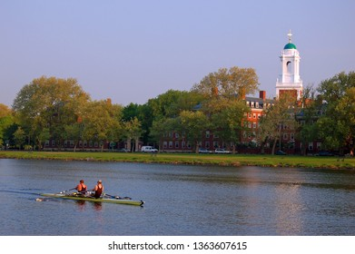 Cambridge, MA, USA May 15, 2007 A double scull plies the Charles River, rowing past Harvard University in Cambridge, Massachusetts