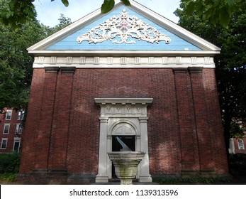 "Cambridge, Massachusetts / USA  - July 21 2018: Holden Chapel in Harvard Yard of Harvard University in Cambridge, Massachusetts, USA, with a sundial in front that reads ""On This Moment Hangs Eternity"""