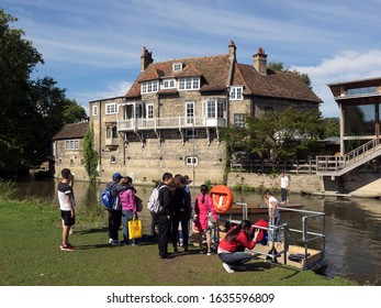 CAMBRIDGE, UK - 08/11/2017:   Tourists queuing at Punt Hire Station waiting to board punt