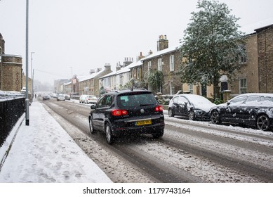 Cambridge, UK -  10 December 2017. UK Weather: Car passing on a road covered in snow during heavy snowing in Cambridge, England,  UK.