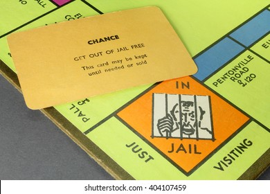 CAMBRIDGE, UK - APRIL 11, 2016: Vintage British Monopoly board (jail corner) and chance card (get out of jail free) circa 1940  - The game play rewards wealth creation - Illustrative Editorial