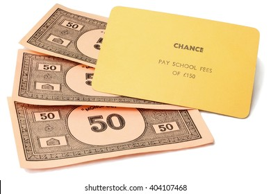 CAMBRIDGE, UK - APRIL 11, 2016: Vintage British Monopoly money and chance card (pay school fees of 150 pounds) circa 1940 - The game play rewards wealth creation - Illustrative Editorial