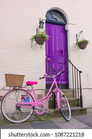 Cambridge, UK -April 2018. Bright pink woman  bicycle with rear wicker basket parked in front of a violet wooden front door of a classic Victorian British style house