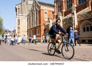 Cambridge, UK -April 2018. People cycling next to Old Divinity School in St Johns street, central Cambridge city centre