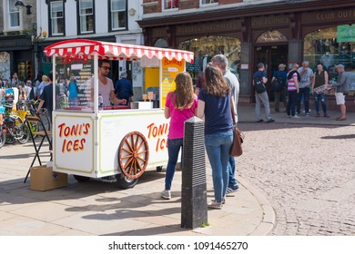 Cambridge, UK -April 2018. People buying ice creams from an ice cream cart vendor provider seller called Toni's ices in Trinity street, central Cambridge, UK