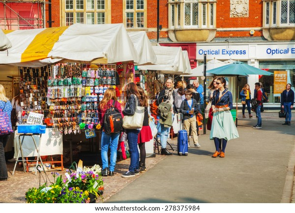 CAMBRIDGE, UK - APRIL 9: Street souvenir shops at the Market square on April 9, 2015 in Cambridge, UK. Cambridge is most widely known as the home of the University of Cambridge, founded in 1209.