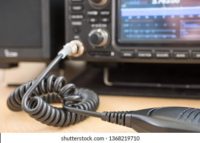 Cambridge, UK - Circa April 2019: Shallow focus of a coiled handheld microphone seen attached to an amateur radio transceiver. Part of the large spectrum display and dials can be seen on the radio.