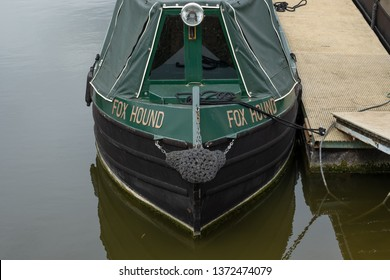 Cambridge, UK - Circa April 2019: Front view of a well maintained narrow boat seen moored in its inland waterway harbour. A walkway can be seen to access to boat, as is a front spotlight.