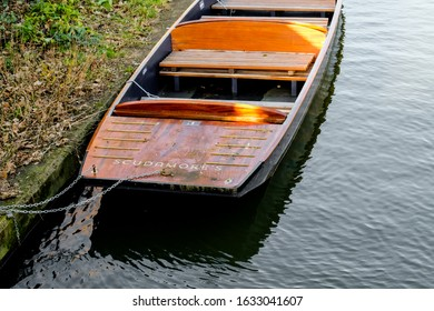 Cambridge, UK - Circa February 2020: Large, wooden Punt seen moored up on a Cambridge river, near the famous Universities. Used for public Punting trips during the warmer months.